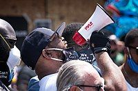 African American man wearing white shouting into bullhorn pointed upper right