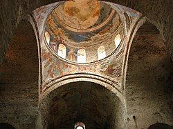 Photograph of a church dome covered with frescoes. From inside the building.