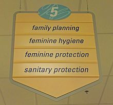 """A yellow sign with a pointed bottom. At the top is the number 5 in an oval with a blue background. Below it are the words """"family planning"""", """"feminine hygiene"""", """"feminine protection"""" and """"sanitary protection"""""""