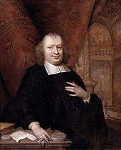 portrait of a plump man standing at a desk with papers lying on it