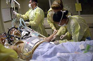 医护人员照顾担架床上一位头部遭受枪伤的患者,已给予气管插管,背景可见使用呼吸器。