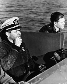 Three men at the con of a boat. One wears a white peaked cap and holds the wheel.