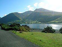 Lush hills beyond a long, narrow lake.