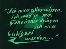 A black screen with green faded shapes in the background, and green words in German language written in angled block letters in the foreground.