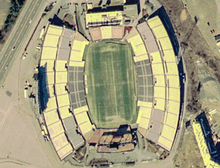Aerial view of Foxboro Stadium with a soccer field surrounded on two sides by three sets of yellow and blue stands, and on two sides by smaller stands.