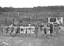 """工人陆续走出厂房,其中绝大多数是女工。他们身后有一张布告牌,上书""""让C.E.W.计数继续保护计划的机密信息!"""""""