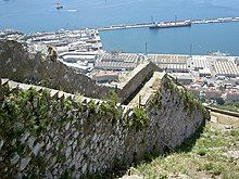 View of a stone wall descending a steep slope, with a harbour in the background