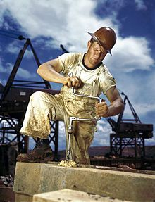 Carpenter in a hard hat using a hand drill outdoors