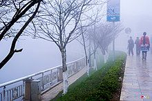 Scene showing fog over a river with people walking on a pathway beside it