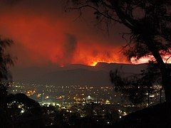 Photograph of evening in a valley settlement. The skyline in the hills beyond is lit up red from the fires.