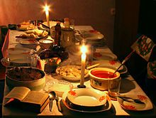 A table covered with a white cloth and set with an open Bible, candles and dishes of various foods