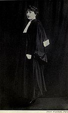 A full-length, black-and-white photograph of a woman wearing judicial robes