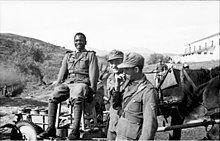An African in German uniform sitting on a chair, next to two other soldiers having a cigarette