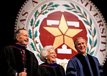 """The head and shoulders of three people - an older man, an older woman, and a middle-aged man - wearing formal robes are shown in front of a large circular seal. On the outer edges of the seal the letters """"XAS A...IVERSITY...87..."""" are visible; an inner band of leaves separates the letters from a block T superimposed with a star."""