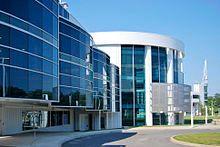 A round white building with dark blue windows, three stories tall.