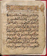 Qur'an page with Arabic text, including a header in gold on a decorated background