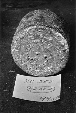 """一块圆柱体金属,圆形的一面朝向镜头。其前方有一张纸,写着""""XC258 42.03wt 99.05%"""""""