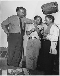 Three men talking. The one on the left is wearing a tie and leans against a wall. He stands with his head and shoulders visibly above the other two's heads. The one in the center is smiling, and wearing an open-necked shirt. The one on the right wears a shirt and lab coat. All three have photo ID passes.