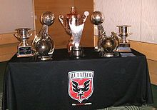 Several bronze trophies sitting on a table with the D.C. United logo