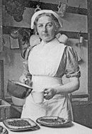 Monochrome photograph of Turner in a cook's apron and hat. She holds a saucepan and a measuring cup. On a table in front of her are several flans, still in their metal dishes