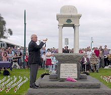 Photo of an ANZAC memorial with an elderly man playing the bugle. Rows of people are seated behind the memorial. Many small white crosses with red poppies have been stuck into the lawn in rows on either side of the memorial.