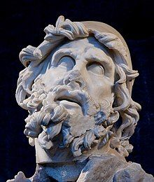 Stone image of the head of a man, showing signs of erosion due to age. The most striking feature is the heavily coiled beard and hair. The eyes are looking sightlessly upwards