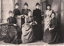 Photograph of seven young Pontic Greek women in western dresses, standing or seated.