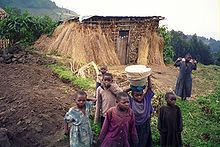 Photograph depicting seven rural children, with a straw house and farmland in the background, taken in the Volcanoes National Park in 2005