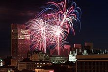 Blue and red fireworks explode over a complex of buildings after dusk.