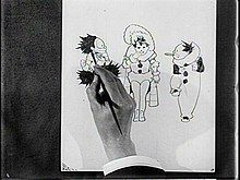 Film still of a hand sketching three cartoon characters