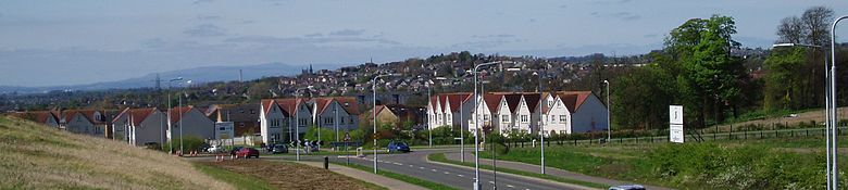 Dunfermline seen from the town's eastern expansion area. The chimney stacks at Grangemouth and Longanett can be seen in the distance