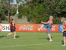 Three players in sports wear on a grassy field. One player has a foot in the air, as if they had just kicked a soccer ball.