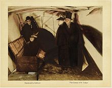 An image of a lobby card with a photograph in the center, and small text captions underneath it. The image shows a man in a dark coat, cape, and top hat standing to the right, while two men investigate another man who is sitting upright inside an open box.