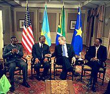 在座的四国总统由左至右分别为:刚果民主共和国总统约瑟夫·卡比拉、南非总统塔博·姆贝基、美国总统乔治·沃克·布什和卢旺达总统保罗·卡加梅。四个国家的国旗位于四人后方。照片中可见美国总统布什正开口发言。