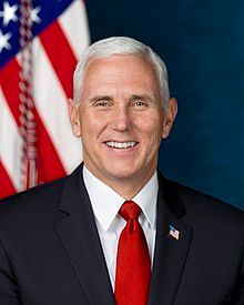 Official White House portrait of Mike Pence smiling. He wears a black suit, red tie, and an American flag lapel pin.