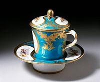 一套圆形的瓷杯,包含杯盖、杯子、杯垫,杯盖盖在杯子上,杯子放在杯垫中。杯盖顶端有形如可可豆的凸起,杯子右侧有弧形的把手,整套瓷杯都绘有植物花纹。