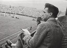 Journalist, seated in the stands and speaking into a microphone
