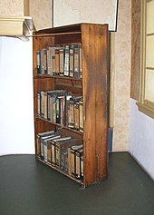 A three shelf timber bookcase, filled with books, stands at an angle in front of a doorway to the Secret Annexe