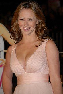 A photograph of a woman in a champagne-colored dress. She is smiling toward the camera.