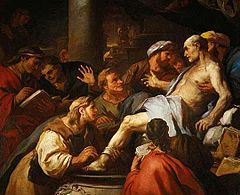 An elderly man, unclothed except for a loose cloth placed on his body, is supported in the arms of an associate, while others crowd around looking anxiously on.