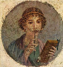 Round painting of a woman with curly hair wearing a gold hairnet while holding a wax writing tablet. She has the stylus in her right hand and the tip in her mouth.