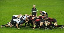 Two opposing formations of eight men, in white and black to the left, red and black to the right, push against each other in a crouched position; behind them stands another player and the referee