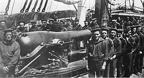 A group of twenty-six sailors posing around a rifled naval cannon