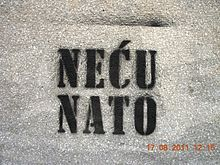 """A white wall with black spray painted words """"Neću Nato"""" on it."""