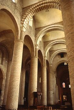 A church interior of yellow stone with arches of alternating red and cream crossing the nave to support an unusual vaulting system.