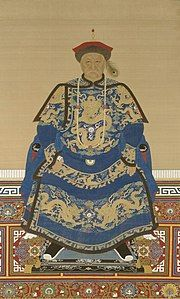 Full-face painted portrait of a severe-looking sitting man wearing a black-and-red round cap adorned with a peacock feather and dressed in dark blue robes decorated with four-clawed golden dragons