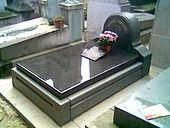 Gravestone in black marble, with small floral tribute on it