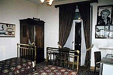Colour photograph of a hotel room with Christie memorabilia on the walls