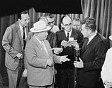A crowd of men surrounds Nikita Khrushchev and Richard Nixon as they hold an impromptu debate
