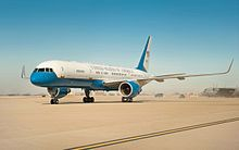 """C-32 taxiing on dusty airport tarmac, showing """"United States of America"""" lettering and tail with U.S. flag."""